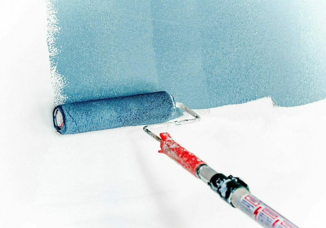 Blue paint roller painting white wall   Residential painters near me